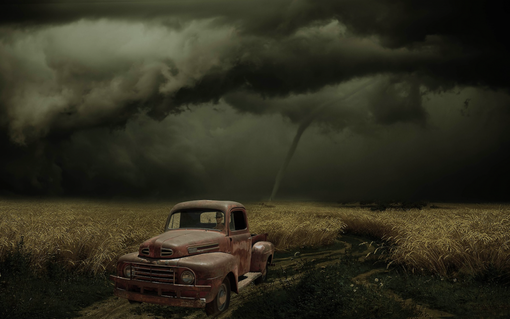 An old car in the middle of a corn field, a very dark sky above